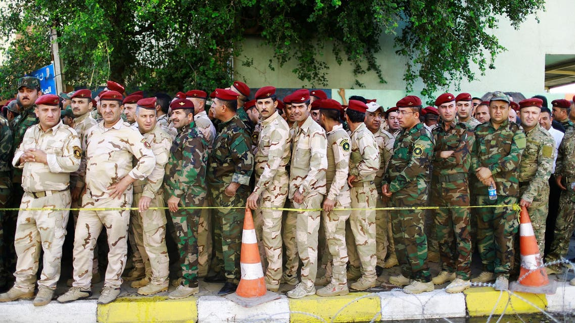 Iraqi security members line up outside a polling station two days before polls open to the public in a parliamentary election in Baghdad on May 10, 2018. (Reuters)