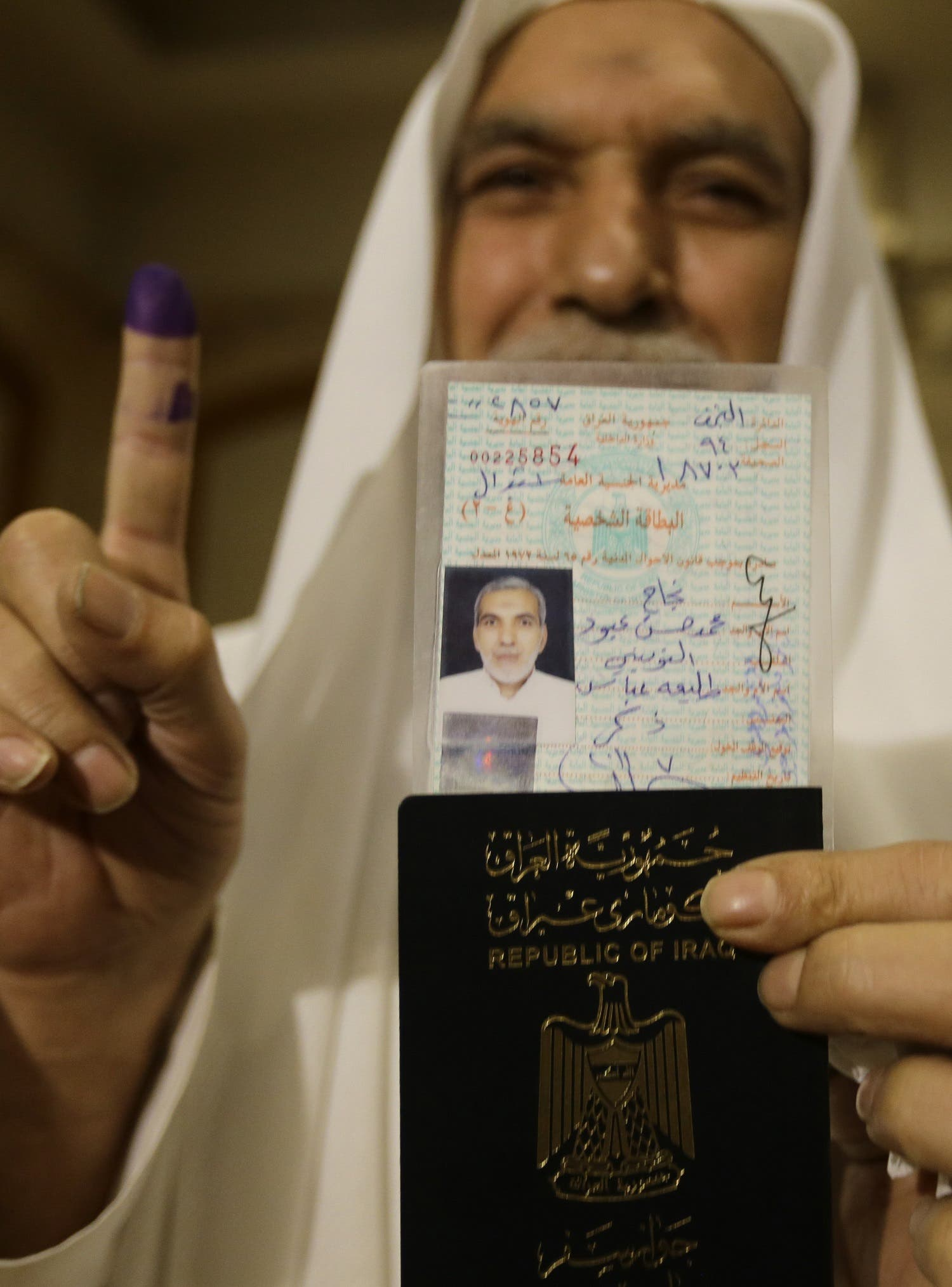 An Iraqi resident of Syria shows his identity papers and his ink-stained index finger after voting in Sayyida Zeinab on the outskirts of Damascus on May 10, 2018. (AFP)