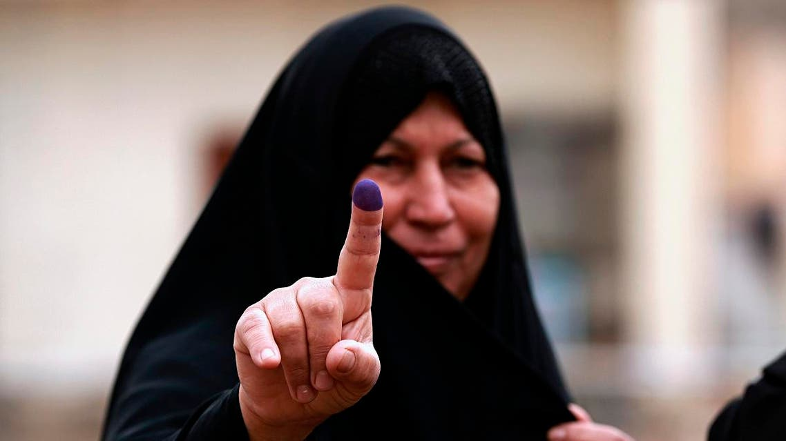An Iraqi woman shows her ink-stained finger after casting her vote in the country's parliamentary elections in Ramadi. (AP)