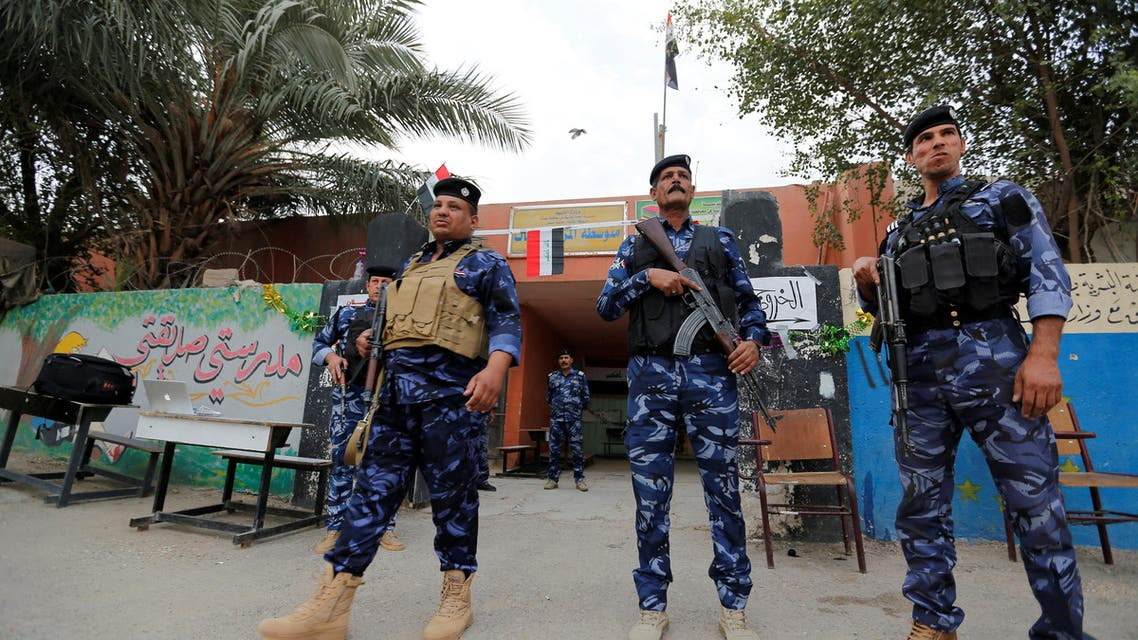 Iraqi security forces stand guard outside a polling station during the parliamentary election in the Sadr city district of Baghdad, Iraq May 12, 2018. REUTERS/Wissm al-Okili