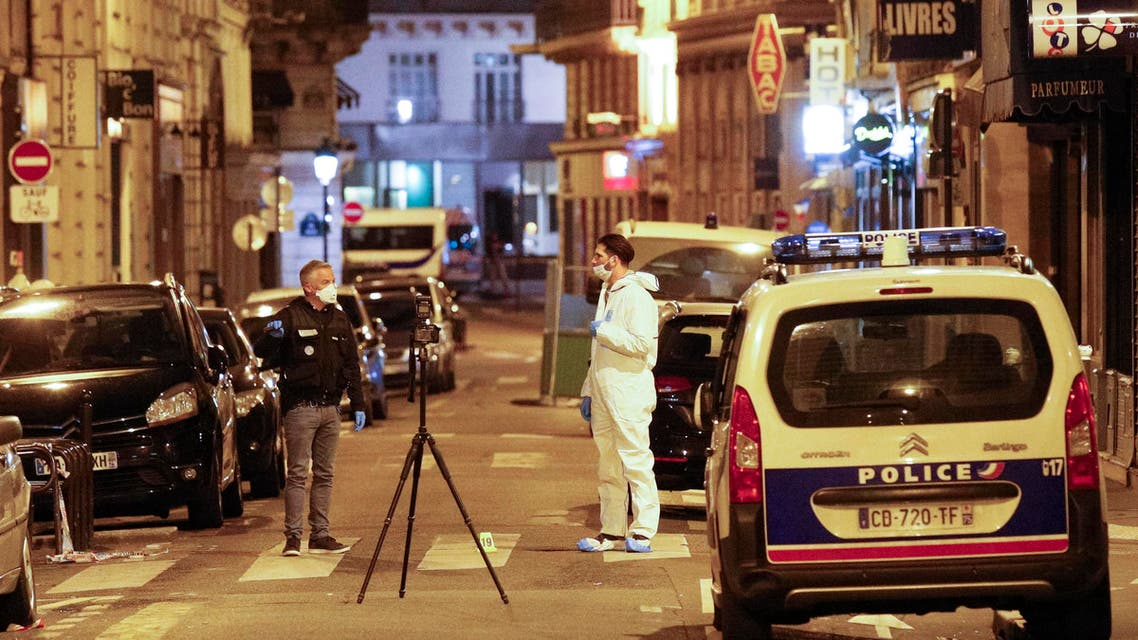 A forensic officer (R) and a French policeman (L) stand next to a numbered reference index pad and a camera on a tripod on Saint Augustin street in Paris after one person was killed and several injured by a man armed with a knife,
