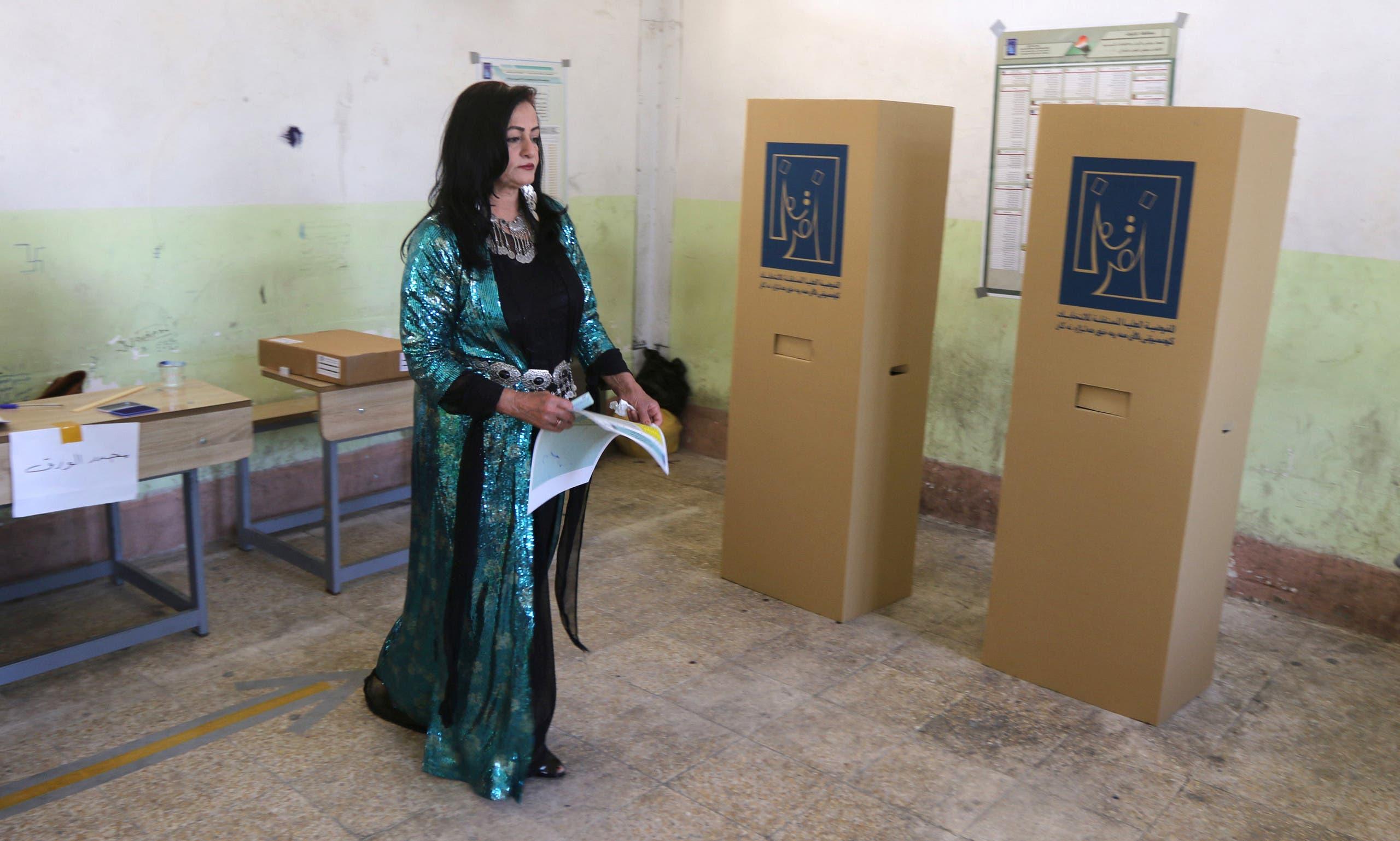 امرأة كردية تستعد للإدلاء بصوتها في مركز اقتراع بكركوك يوم السبت