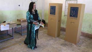 امرأة كردية تستعد للإدلاء بصوتها في مركز اقتراع بكركوك السبت