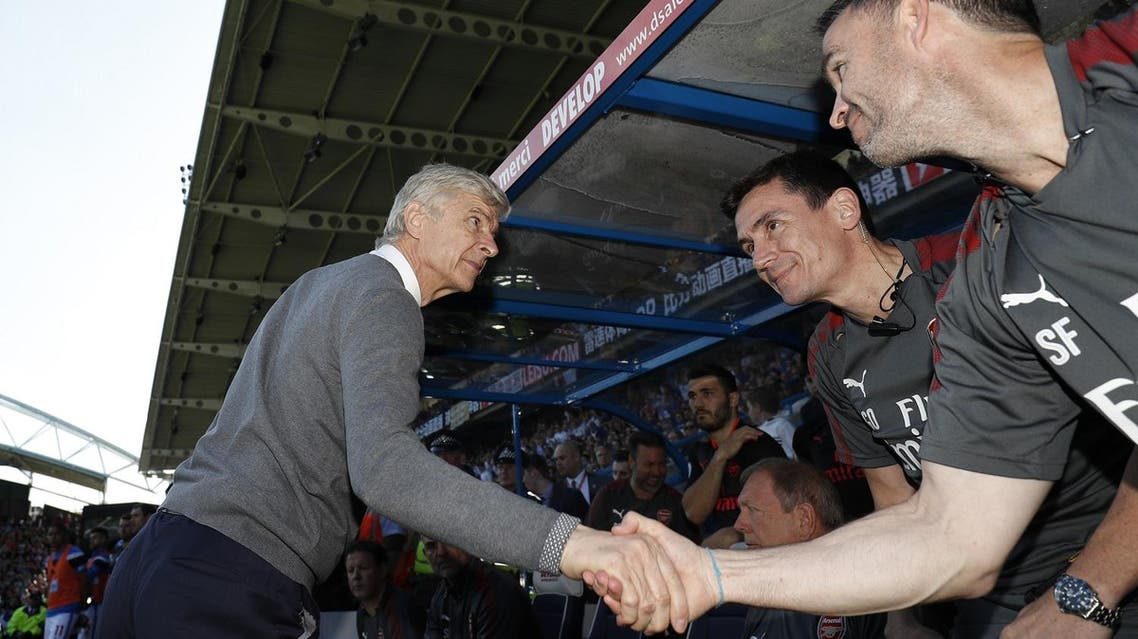 Arsenal's French manager Arsene Wenger shakes hands with his staff during the English Premier League football match against Huddersfield Townon May 13, 2018. (AFP)