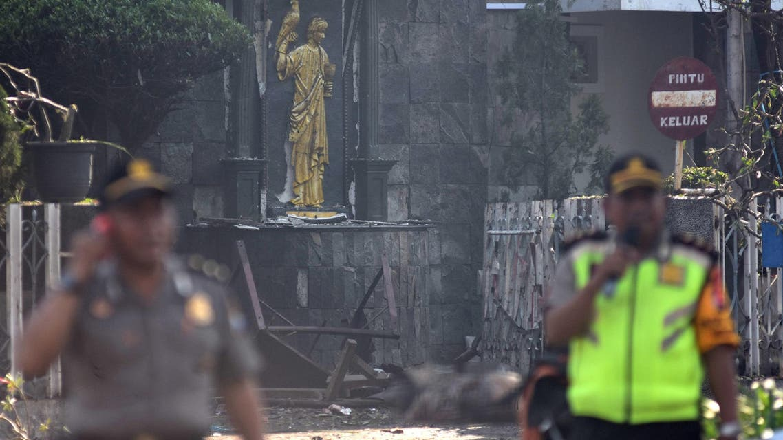 Police are seen outside the Immaculate Santa Maria Catholic Church following a blast, in Surabaya. (Reuters)