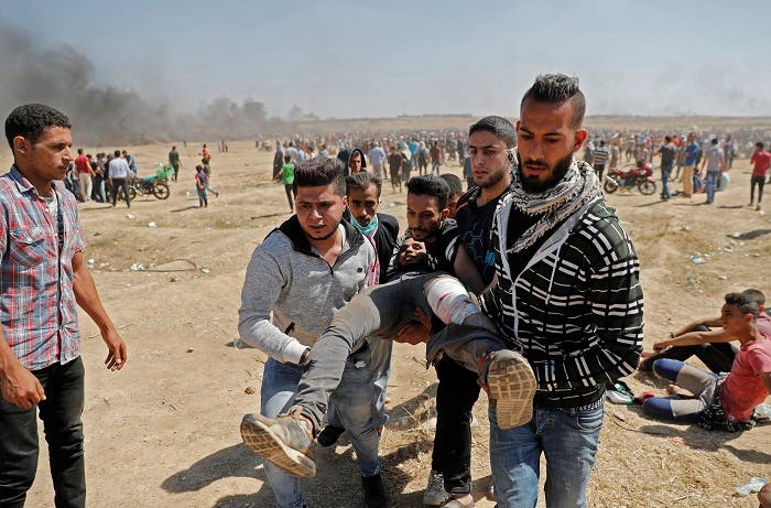 Palestinians carry a demonstrator injured during clashes with Israeli forces near the border between the Gaza strip. (AFP)