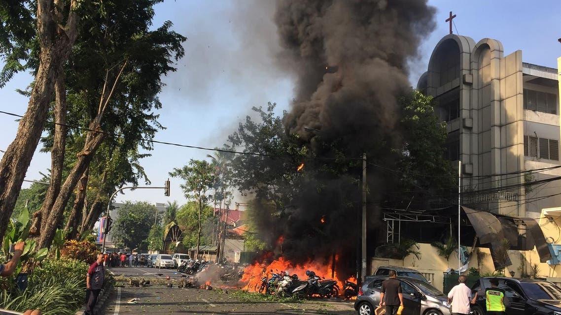 police at the site of a blast outside the Gereja Pantekosta Pusat Surabaya (Surabaya Centre Pentecostal Church) in Surabaya. AFP