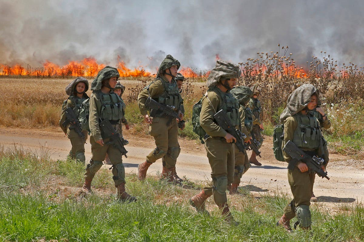 Israeli soldiers walk amidst smoke from a fire in a wheat field near the Kibbutz of Nahal Oz, along the border with the Gaza. (AFP)