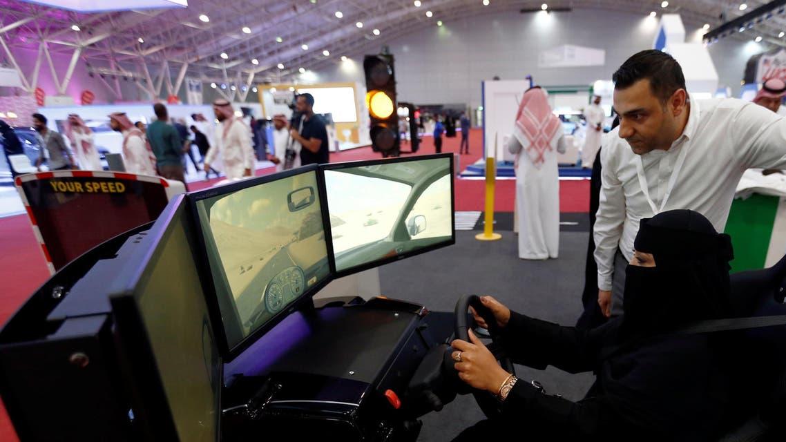 A Saudi woman tries a car simulator during women car show in Riyadh. (Reuters)