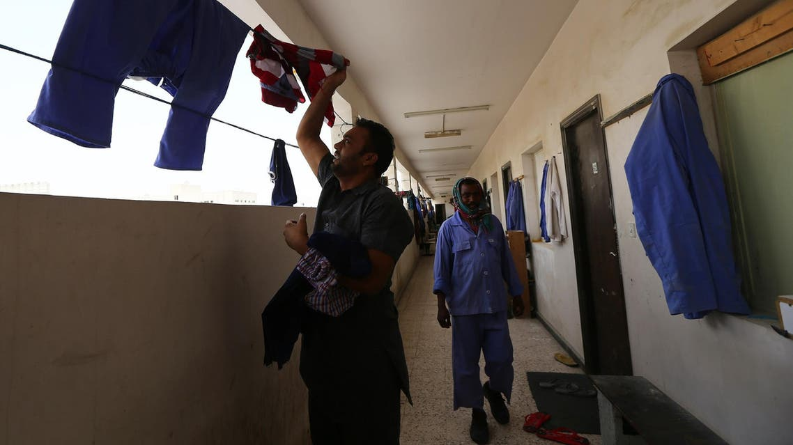 An Indian labourer collects his clothes hanging outside rooms at a private camp housing foreign workers in Doha, on May 3, 2015. (File photo: AFP)