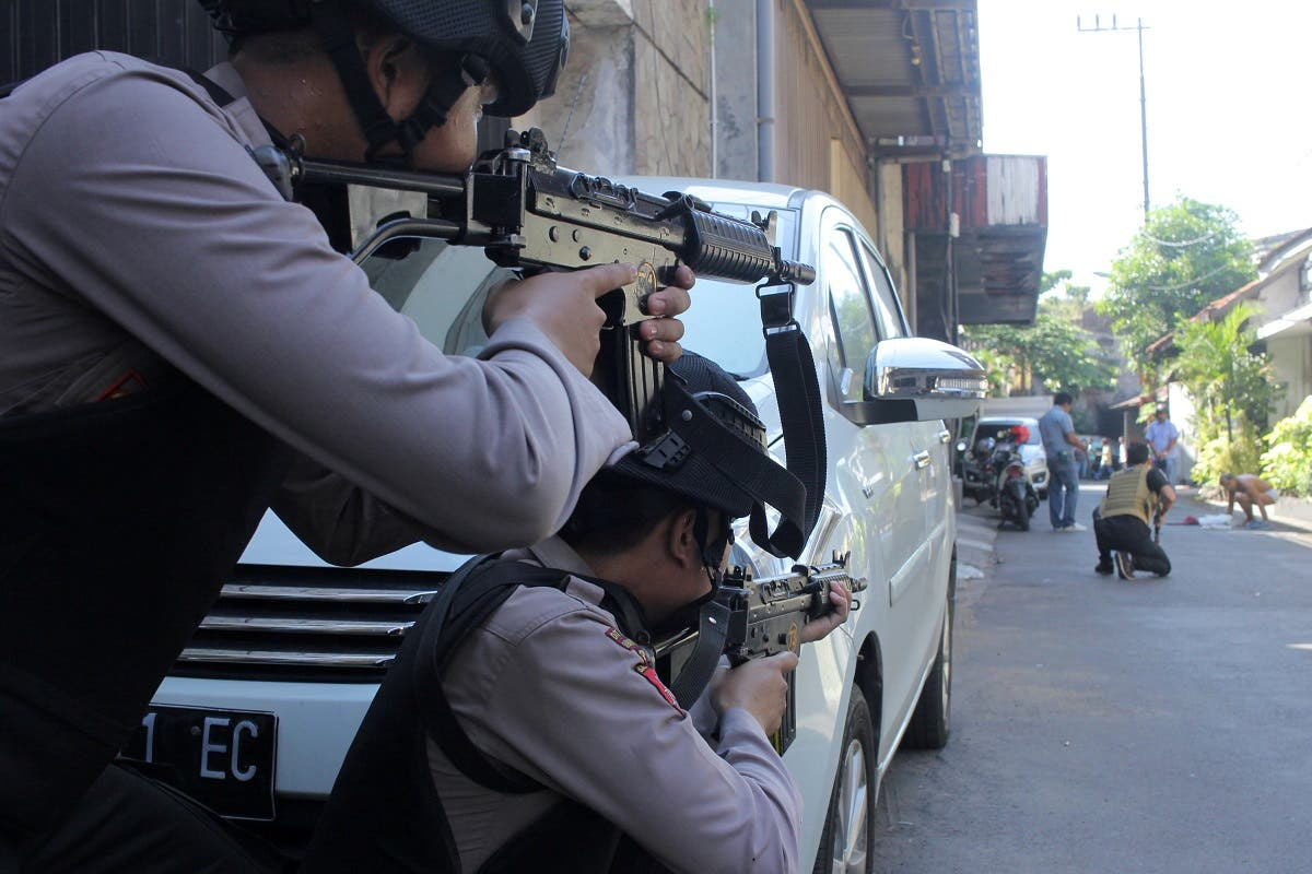 Police aim their weapons at a man who was being searched by other police officers following an explosion at nearby police headquarters in Surabaya. (Reuters)