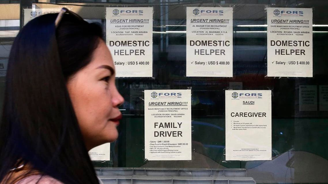 A woman passes help wanted signs outside a recruitment agency for jobs abroad in Manila. (AP)