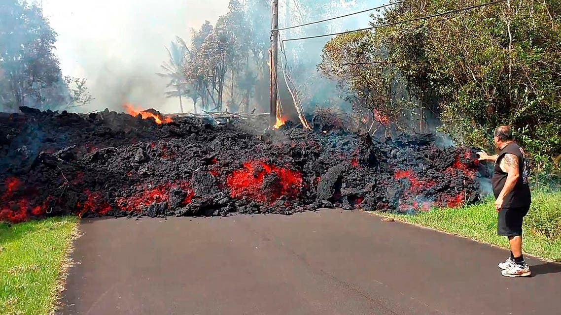 man gets close to a lava flow advancing down a road in the Leilani Estates subdivision near Pahoa on the island of Hawaii Monday, May 7, 2018. (AP)