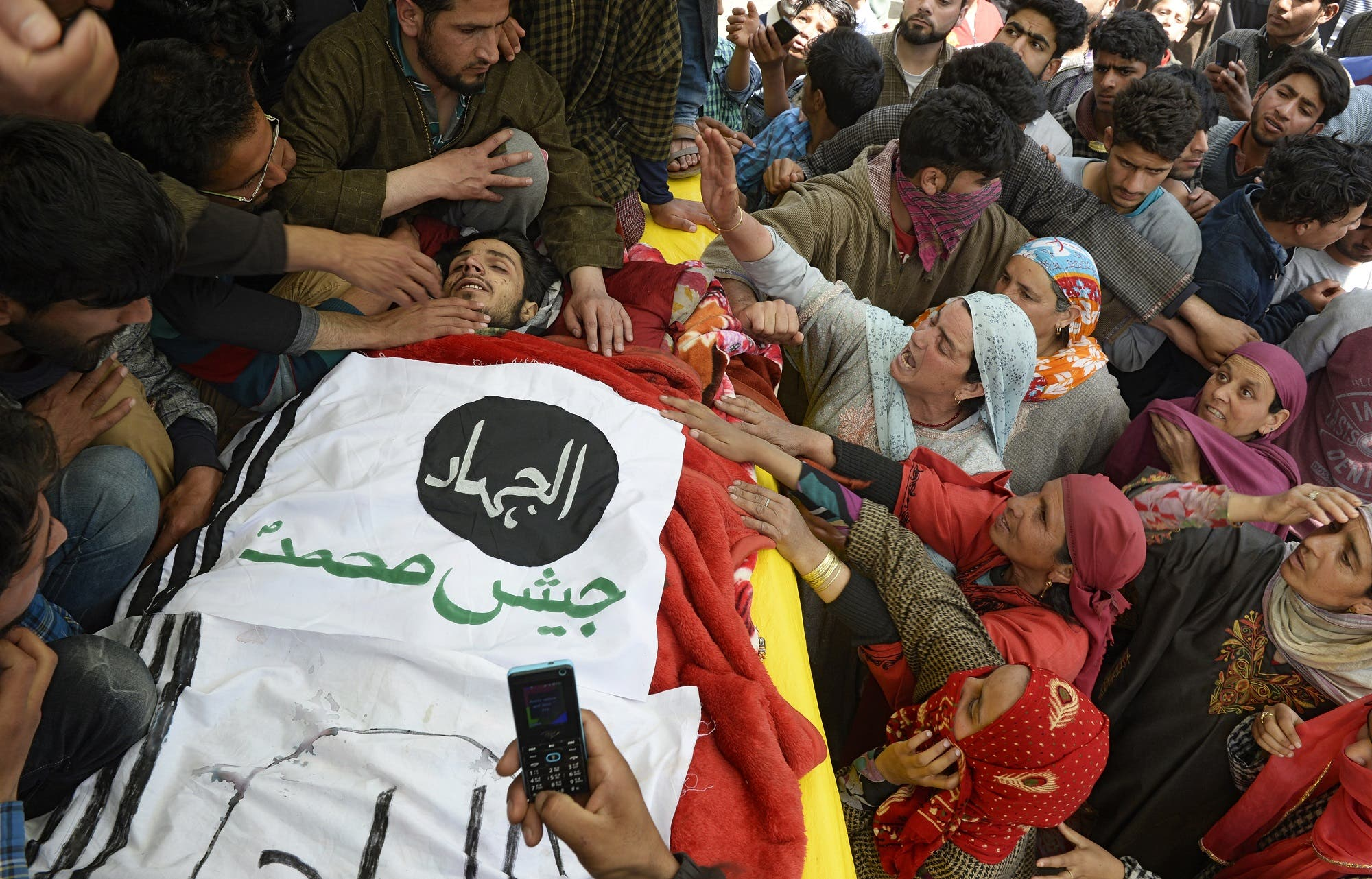 Kashmiri women try to touch the face of a slain militant during his funeral in Tral district south of Srinagar on April 25, 2018. (AFP)