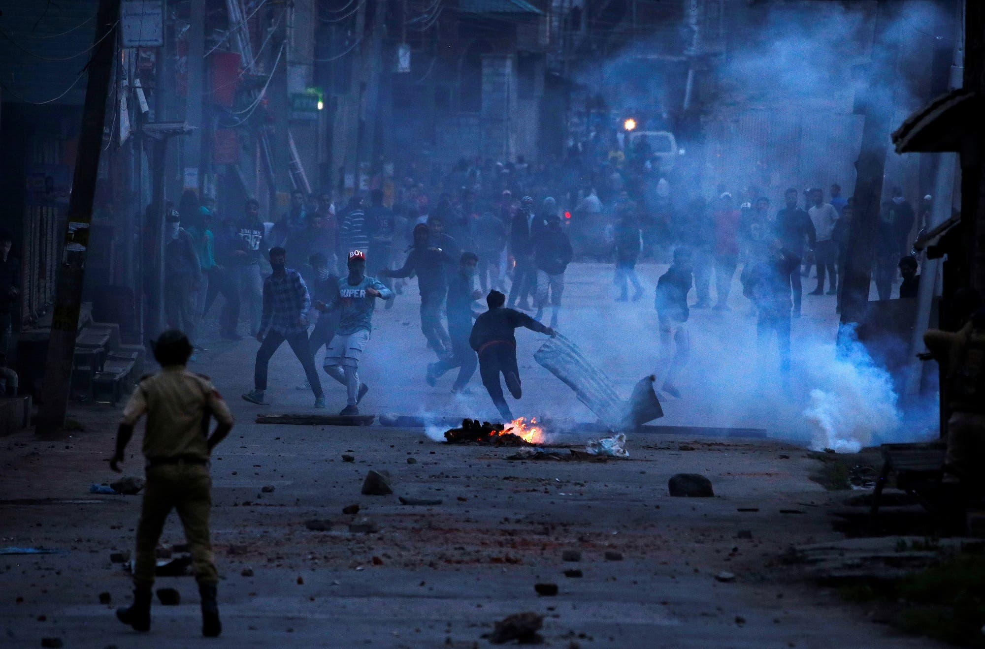 Demonstrators throw stones towards the Indian police during a protest against the recent killings in Kashmir, in Srinagar, on May 8, 2018. (Reuters)