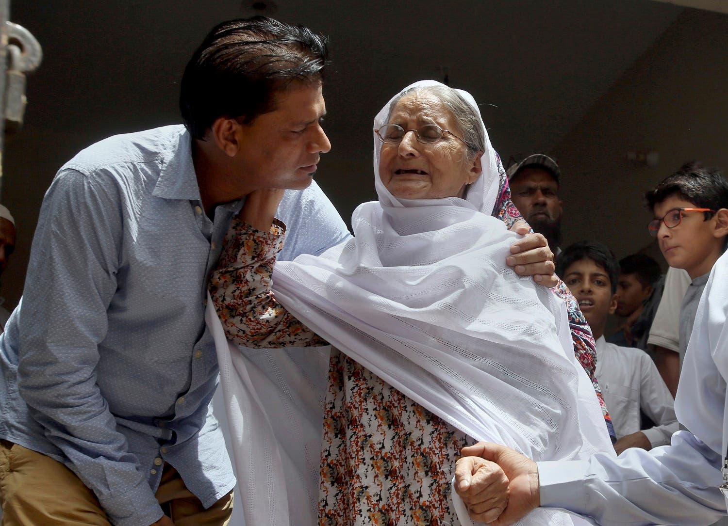 Abdul Aziz Sheikh, left, father of Sabika Sheikh, a victim of a shooting at a Texas high school, comforts to an elderly woman arriving for condolence at his home in Karachi. (AP)