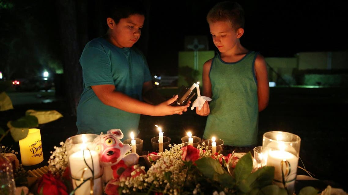 Christian Cardenas 10, helps Jaydon Johnson 8, light a candle during a vigil for the victims of a shooting at Santa Fe High School that left several dead and injured in Santa Fe, Texas, US, on May 18, 2018. (Reuters)