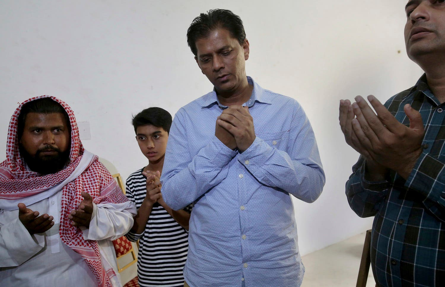 Abdul Aziz Sheikh, center, father of Sabika Sheikh, a victim of a shooting at a Texas high school, prays with other relatives at his home in Karachi. (AP)