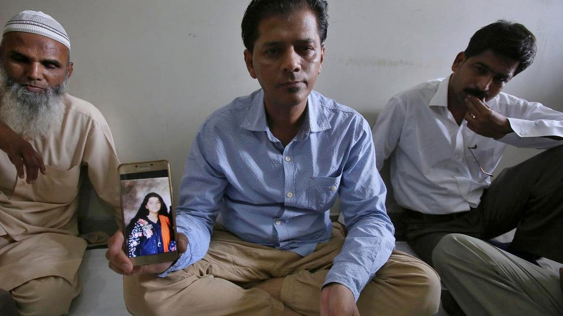 Abdul Aziz Sheikh, center, father of Sabika Sheikh, a victim of a shooting at a Texas high school, shows a picture of his daughter in Karachi, Pakistan, on May 19, 2018. (AP)