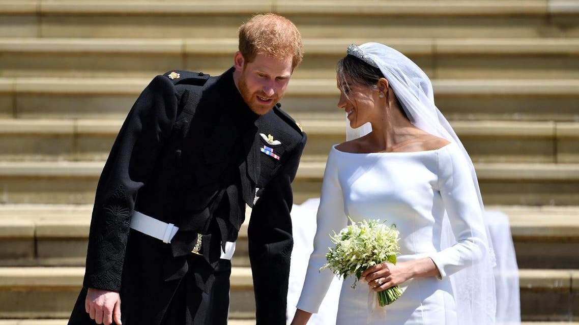 Britain's Prince Harry, Duke of Sussex and his wife Meghan, Duchess of Sussex walk down the west steps of St George's Chapel.