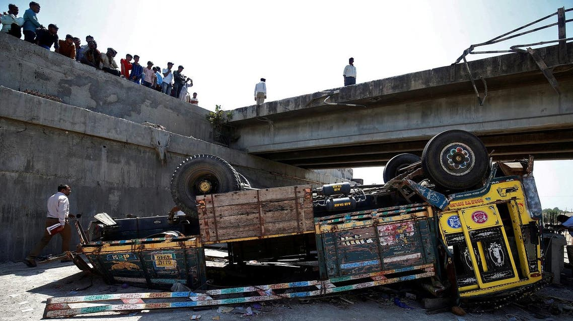 Police officers inspect the site of an accident after a truck carrying wedding party guests plunged into a dry riverbed, in Ranghola village in Bhavnagar district, in the western Indian state of Gujarat, India, on March 6, 2018. (Reuters)