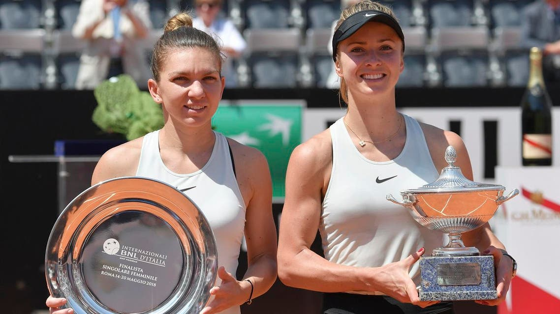 Elina Svitolina (R) holds the trophy next to Simona Halep after winning the women's final at Rome's WTA Tennis Open tournament at the Foro Italico, on May 20, 2018. (AFP)