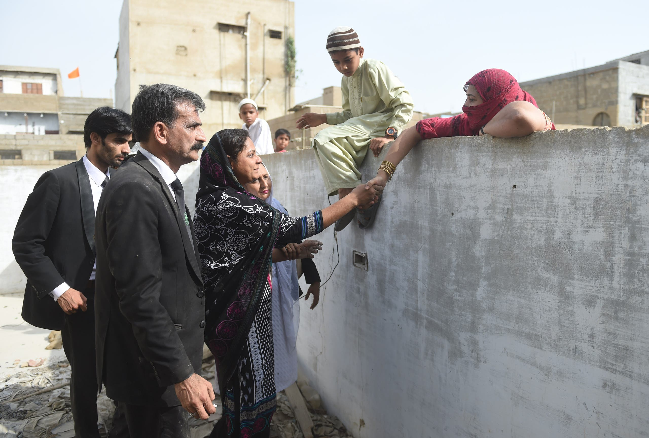 asma nawab with her lawyer and shaking hand with her neighbor. (AFP)