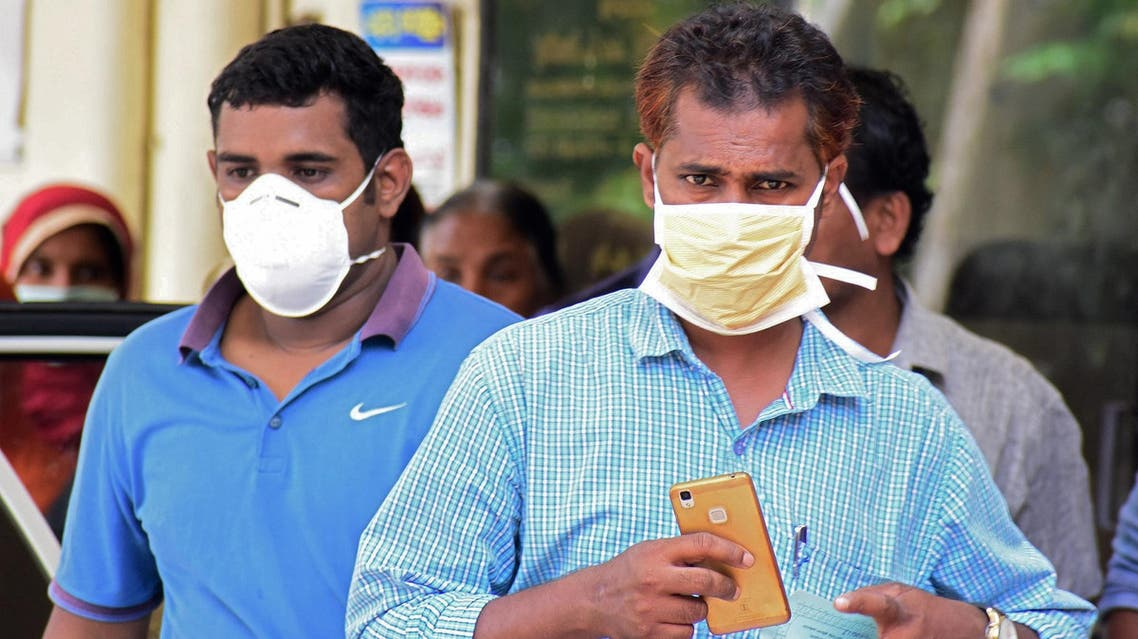 Indian residents wear face mask outside the Medical College hospital in Kozhikode on May 21, 2018. (AFP)