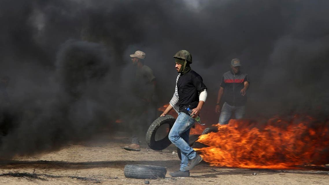 Palestinian protesters burn tires near the fence at the Gaza Strip's border with Israel, during a protest on the first Friday of the holy month of Ramadan, east of Khan Younis, in the Gaza Strip, on May 18, 2018. (AP)