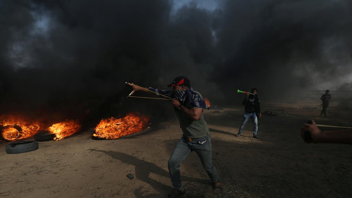 A demonstrator uses a slingshot to hurl stones during a protest where Palestinians demand the right to return to their homeland, at the Israel-Gaza border, in the southern Gaza Strip May 18, 2018. REUTERS/Ibraheem Abu Mustafa