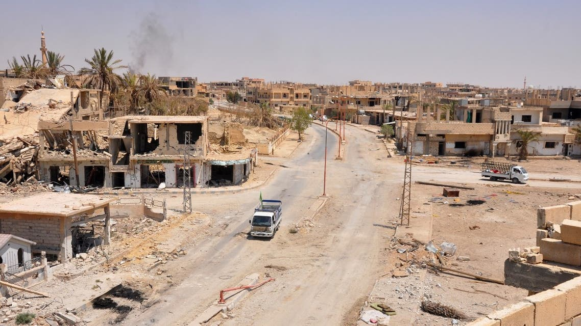 A general view taken on August 13, 2017, shows a vehicle driving down a damaged street in the central Syrian town of Al-Sukhnah, situated in the county's large desert area called the Badiya, as pro-government forces clear the area after taking control of the city from Islamic State (IS) group fighters. Supported by regime ally Russia, Syria's army has waged a months-long offensive to recapture the vast desert region that stretches from the country's centre to the Iraqi and Jordanian borders.