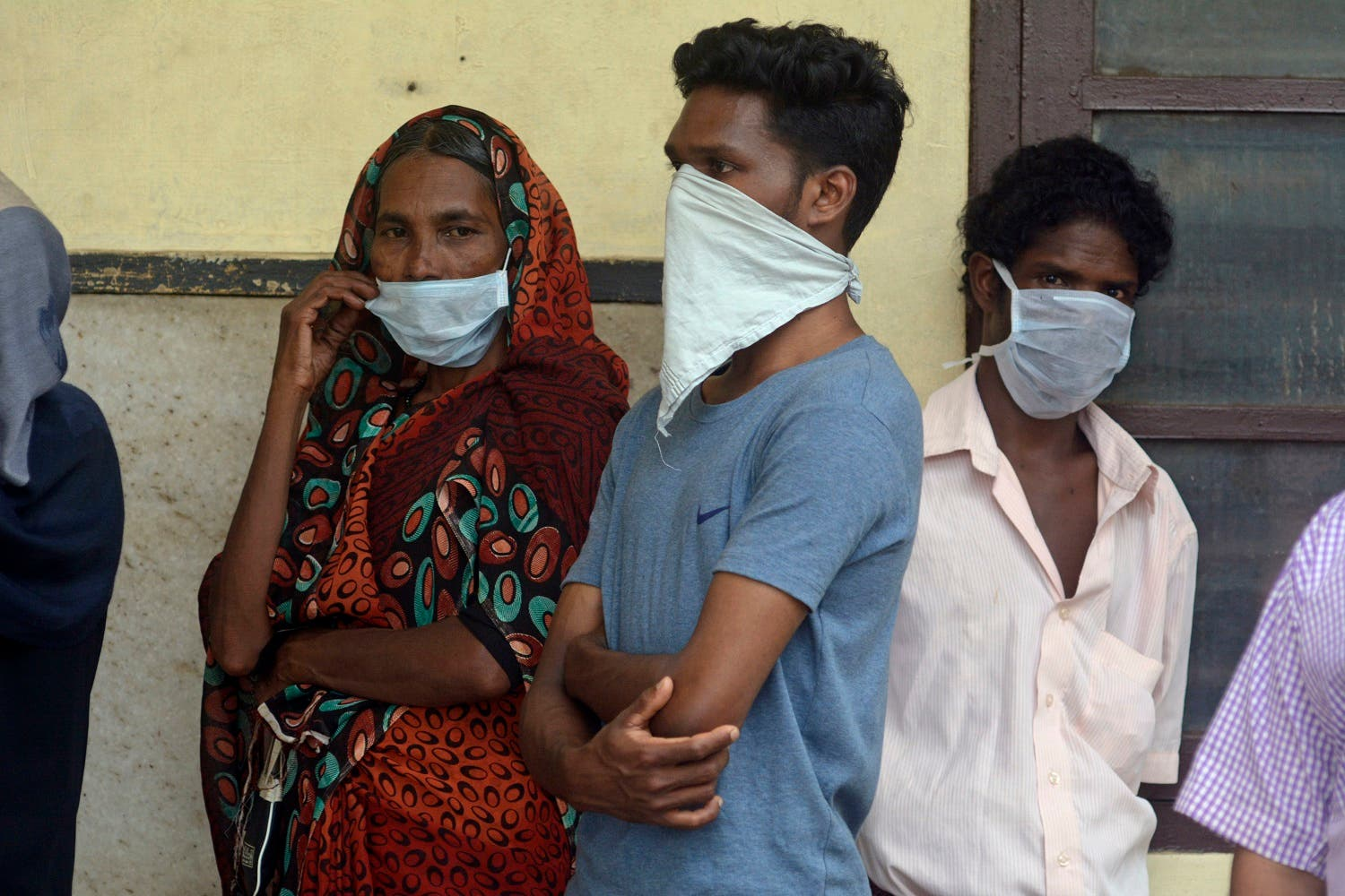 People in India stand outside a hospital wearing masks as a precautionary measure against the Nipah virus on May 21, 2018. (AP)
