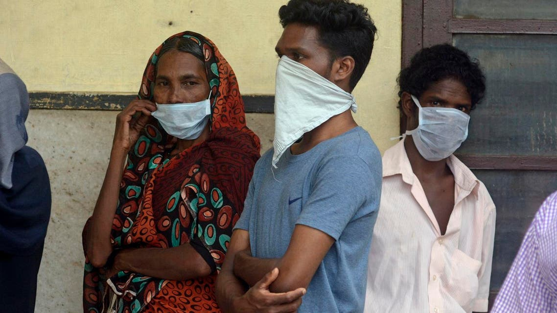 Indians standing in a queue outside a hospital wear masks as a precautionary measure against the Nipah virus at the Government Medical College hospital in Kozhikode, in the southern Indian state of Kerala, Monday, May 21, 2018. (AP)