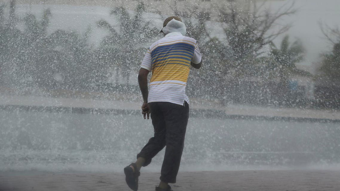 A man covers his head under the rain in Salalah, Oman, Friday, May 25, 2018. Cyclone Mekunu pounded the Yemeni island of Socotra in the Arabian Sea on Thursday morning, lashing it with heavy rain and strong winds as the powerful storm remained on a path to strike Oman this weekend. At least 17 people were reported missing. (AP Photo/Kamran Jebreili)