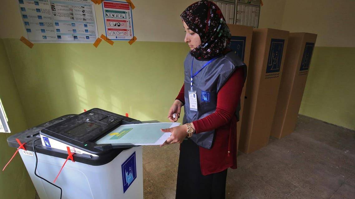 An Iraqi election registrar places a ballot through an electronic counting machine at a polling station in Mosul on May 12, 2018. (AFP)