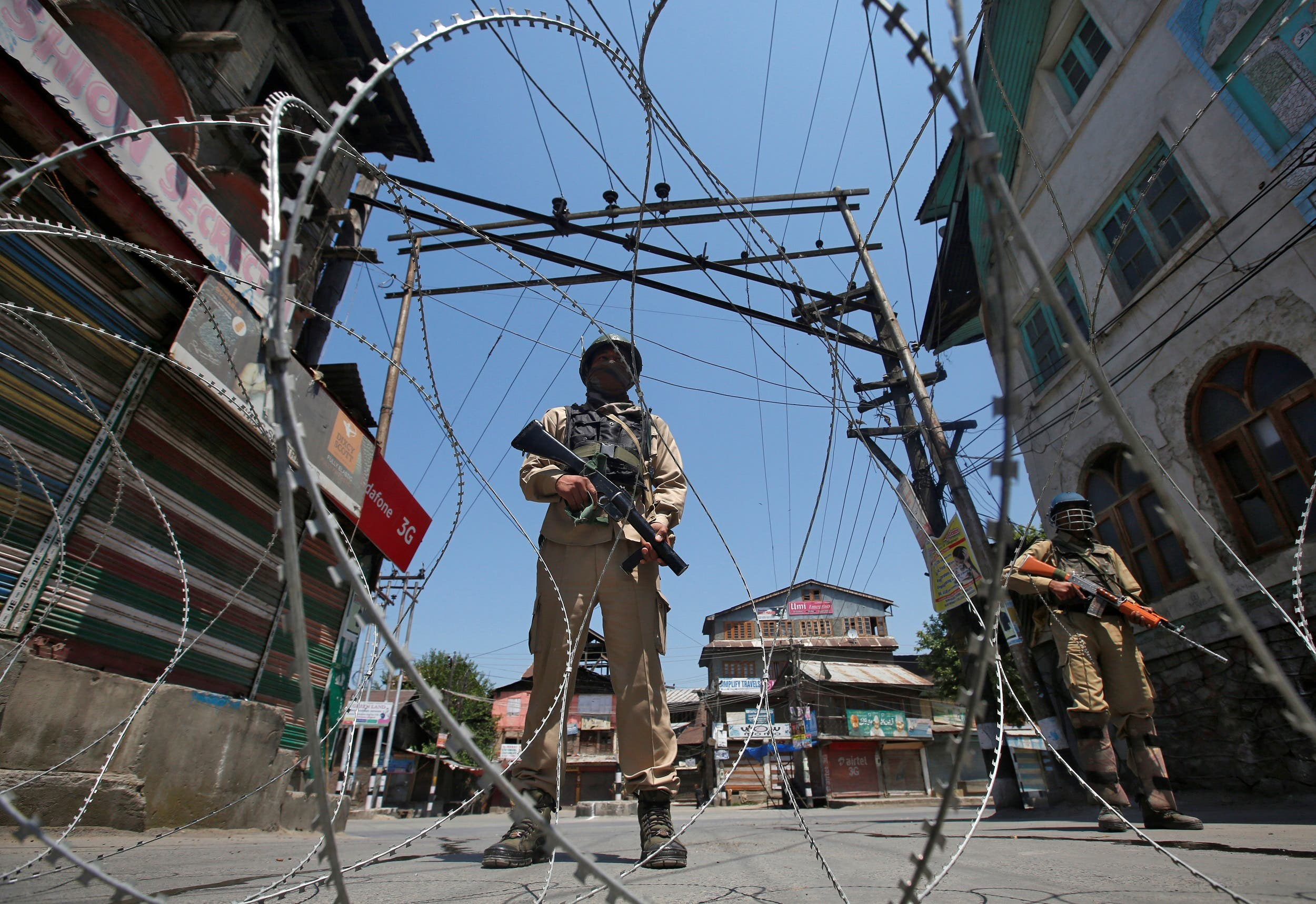 Indian policemen stand guard behind concertina wire during a strike in Srinagar on May 21, 2018. (Reuters)