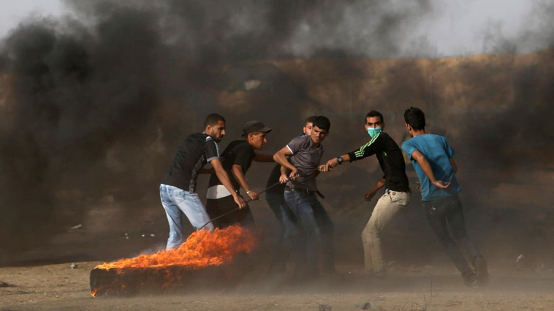 Palestinian demonstrators drag a burning tire during a protest demanding the right to return to their homeland, at the Israel-Gaza border in the southern Gaza Strip May 25, 2018. REUTERS/Ibraheem Abu Mustafa TPX IMAGES OF THE DAY