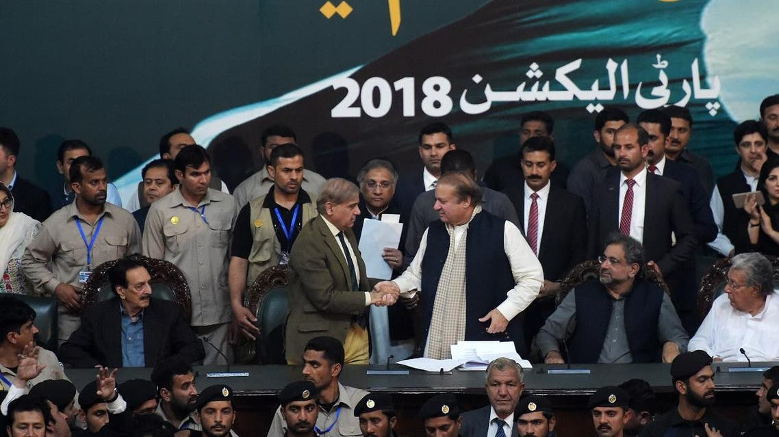 Pakistani Chief Minister of Punjab province Shahbaz Sharif, shakes hands with his brother and ousted prime minister Nawaz Sharif (3R) while Prime Minister of Pakistan Shahid Khaqan Abbasi (2R) looks on, after being elected President of ruling Pakistan Muslim League-Nawaz (PML-N) party at the General Workers Council in Islamabad on March 13, 2018. (AFP)