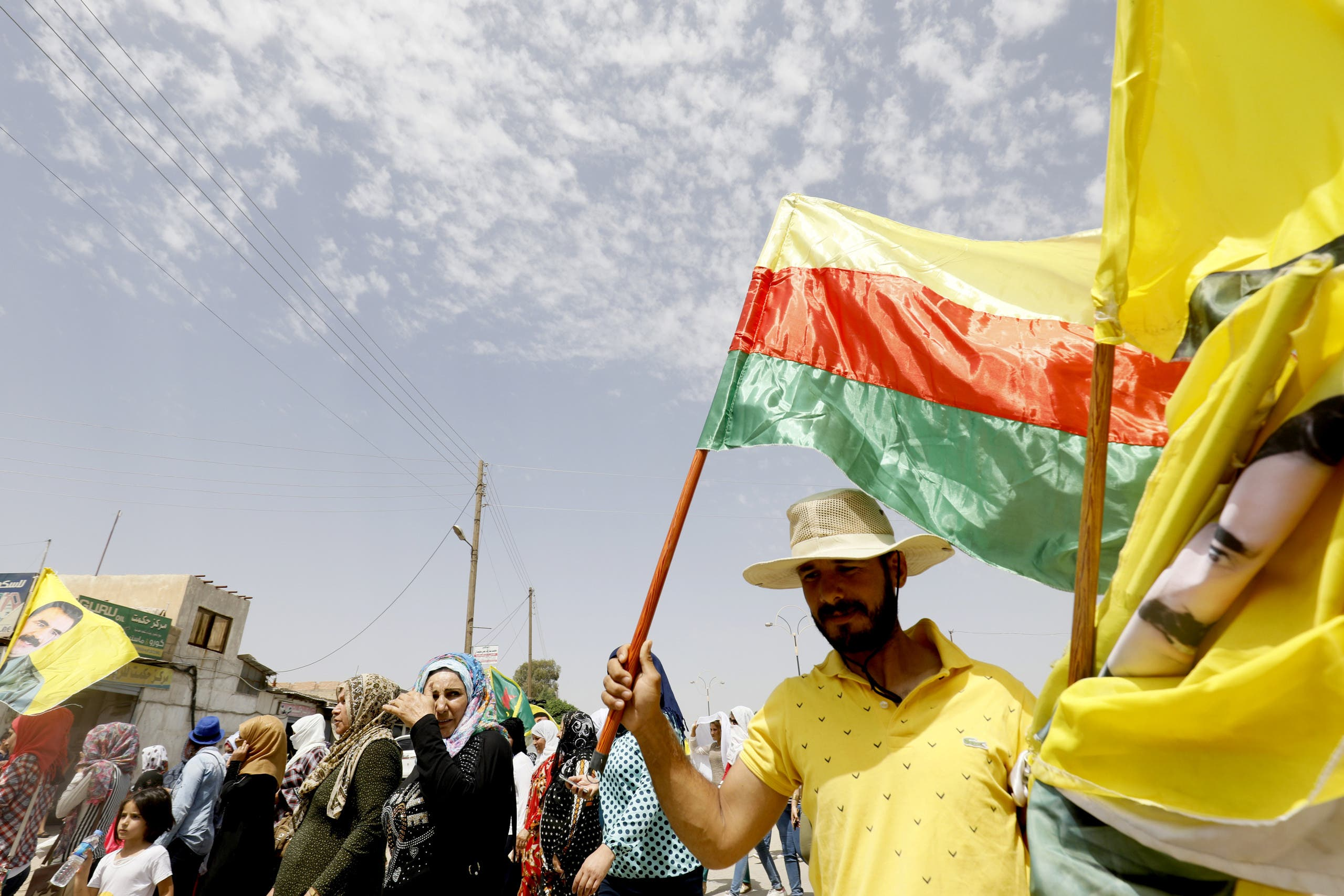 A Syrian-Kurdish man holds a Kurdish flag as well as flags with the face of Kurdistan Worker's Party (PKK) leader Abdullah Ocalan as people demonstrate against demographic changes forced by Turkey to repopulate Kurdish areas, in Qamishli on May 26, 2018. Delil souleiman / AFP