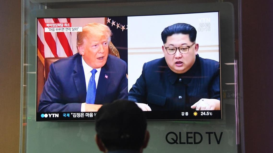 A man watches a television news screen showing US President Donald Trump (L) and North Korean leader Kim Jong Un (R). (AFP)