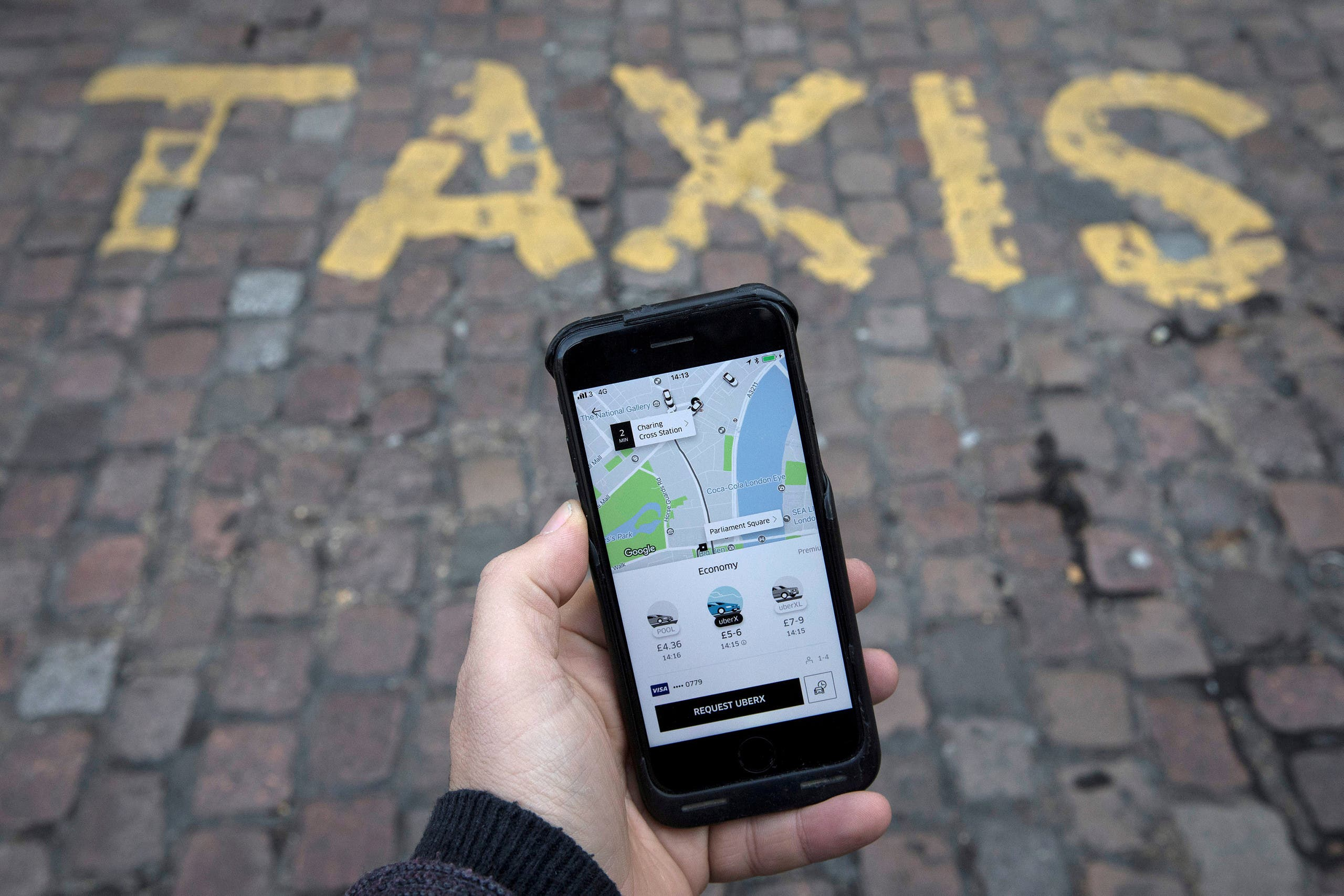 A photo illustration shows the Uber app on a mobile telephone, as it is held up for a posed photograph, in London on November 10, 2017. (Reuters)
