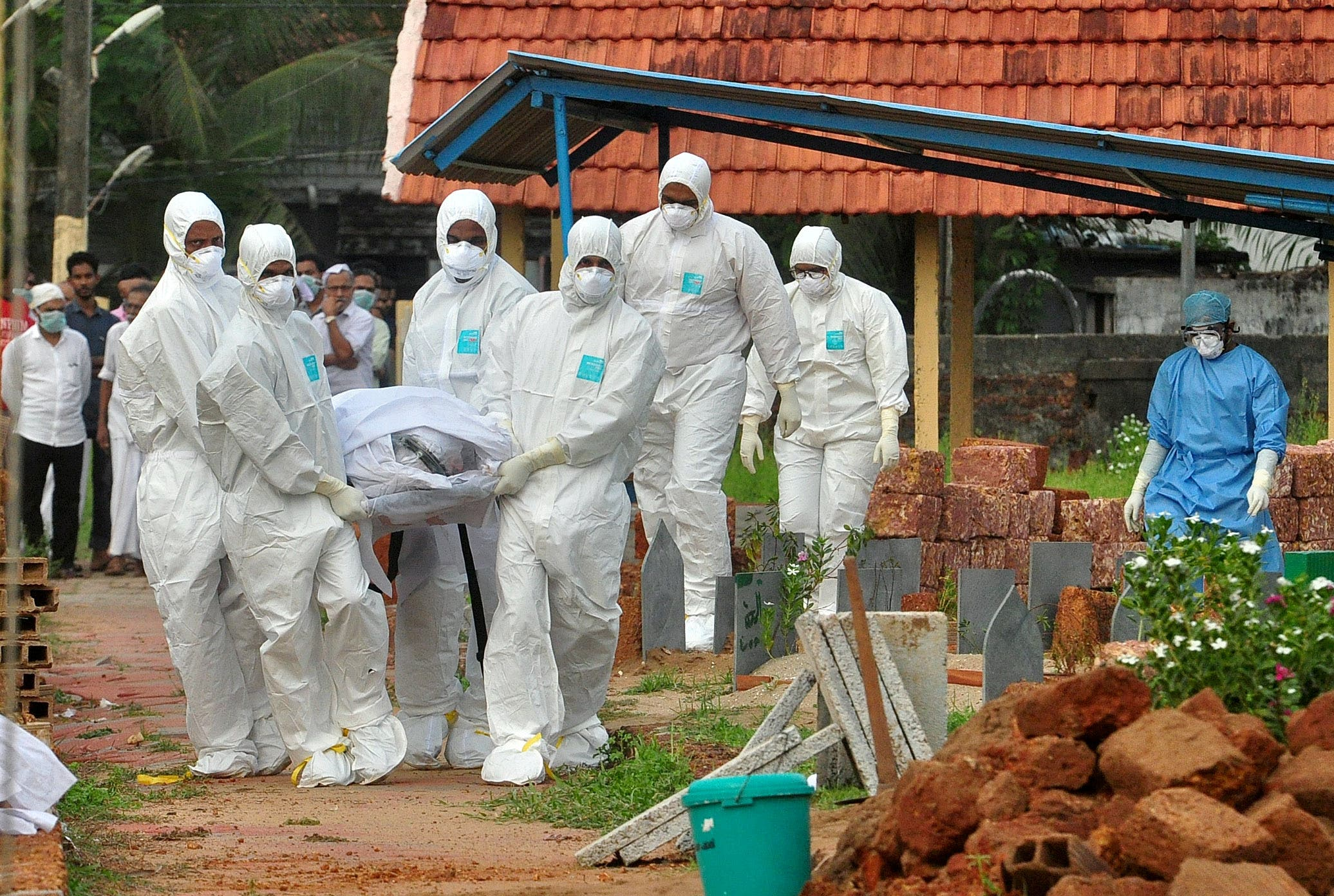 Doctors and relatives wearing protective gear carry the body of a victim, who lost his battle against the brain-damaging Nipah virus, during his funeral at a burial ground in Kozhikode, in the southern Indian state of Kerala, India. (File photo: Reuters)