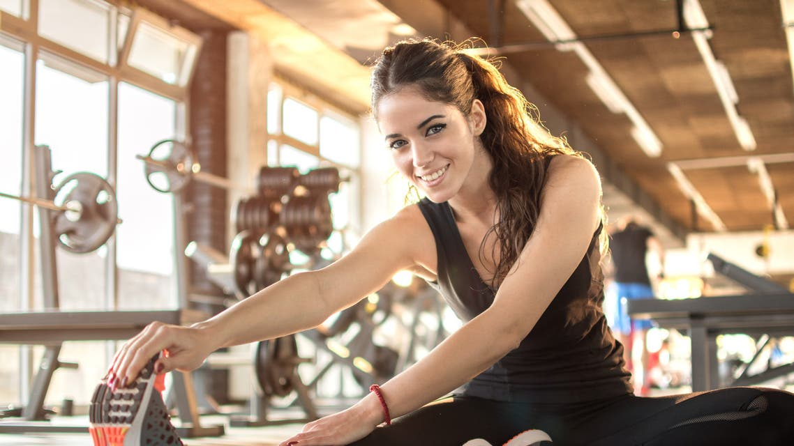 Young sporty woman stretching at gym. - Stock image