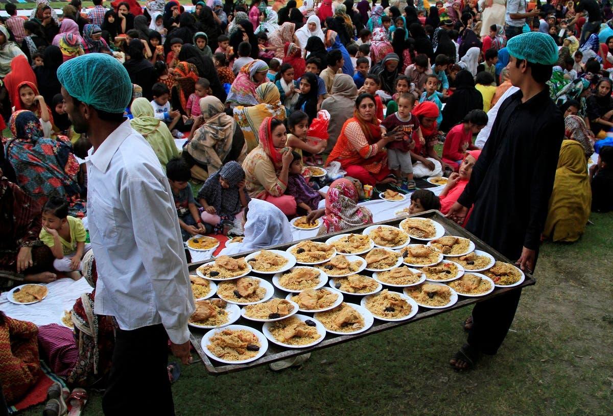 توزیع غذا در میان زنان و کودکان برای افطار در پارکی در لاهور پاکستان