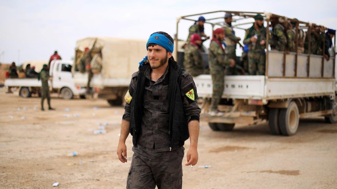A fighter of Syrian Democratic Forces (SDF) walks in Deir al-Zor, Syria May 1, 2018. REUTERS/Rodi Said