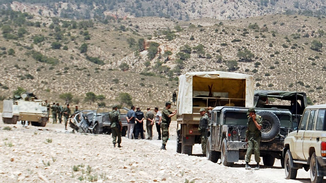 Tunisian army stand guard near a demolished vehicle following a roadside bomb in the mountainous border region near Algeria where security forces have been hunting Al-Qaeda linked jihadists, on June 6, 2013. Two soldiers were killed and two others wounded when a device exploded as their vehicle passed by in the Doghra area of Mount Chaambi. AFP PHOTO / ABDERRAZEK KHLIFI