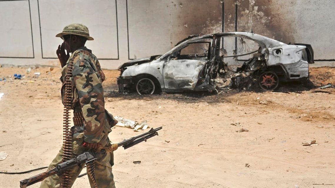 A Somali soldier patrols next to the burnt-out wreckage of a car that was used by suspected al-shabab fighters on April 16, 2017. (AFP)
