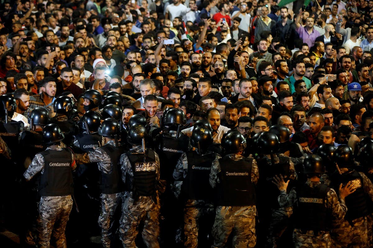 Demonstrators stand face to face with riot police during a protest in front of the Prime Minister's office in Amman. (Reuters)
