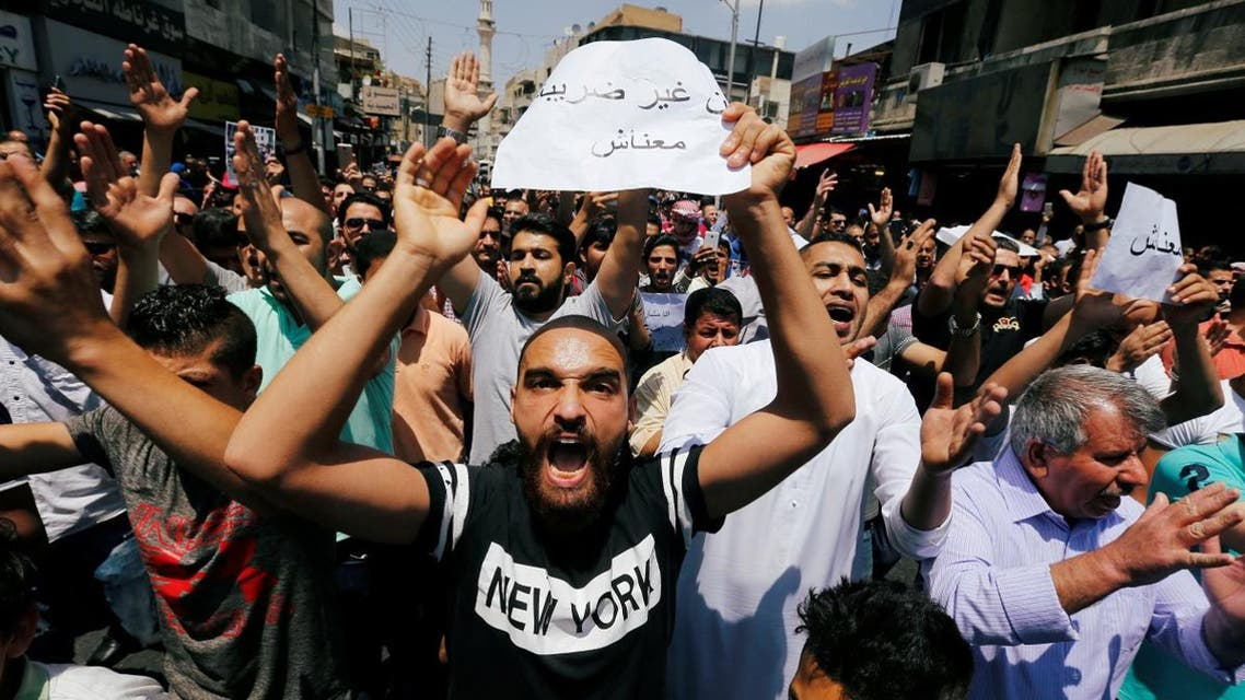 Protesters chant slogans during a protest against the new income tax law and high fuel prices, in Amman. (Reuters)