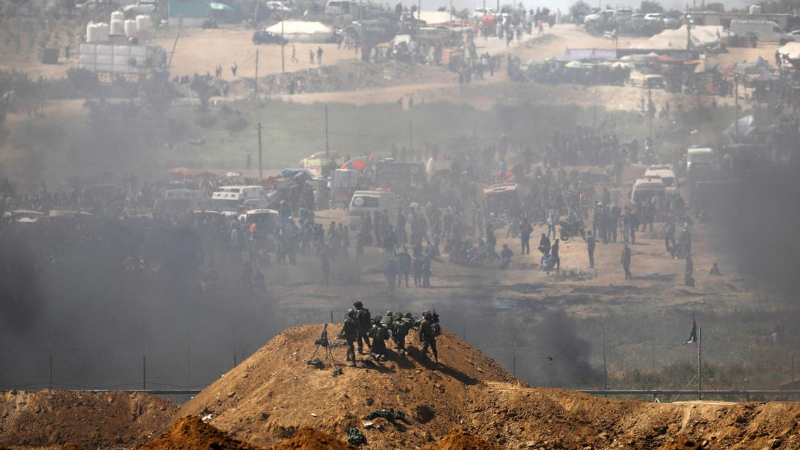 Gaza Border, Israel Israeli soldiers are seen next to the border fence on the Israeli side of the Israel-Gaza border as Palestinians protest on the Gaza side of the border April 6, 2018. (Reuters)